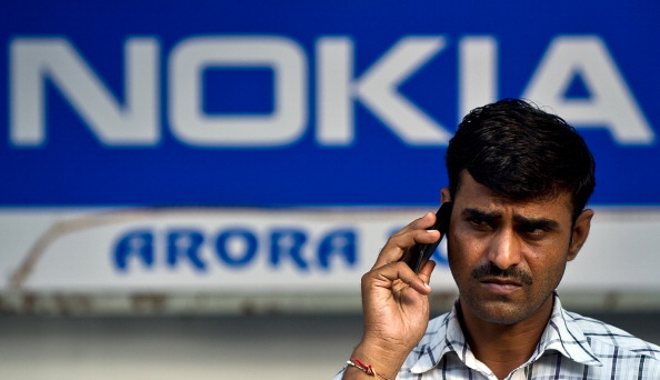 An Indian pedestrian talks on his mobile phone outside a Nokia store in New Delhi on October 1, 2013. Indian authorities have frozen some of Finnish telecom giant Nokia's assets, the company said, amid a 20-billion rupee ( USD 321 million) tax dispute with the New Delhi government. AFP PHOTO/ MANAN VATSYAYANA (Photo credit should read MANAN VATSYAYANA/AFP/Getty Images)